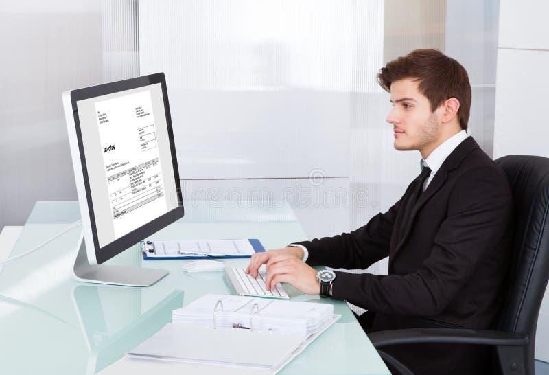 Ung affärsman som använder på datoren på skrivbordet arkivbild