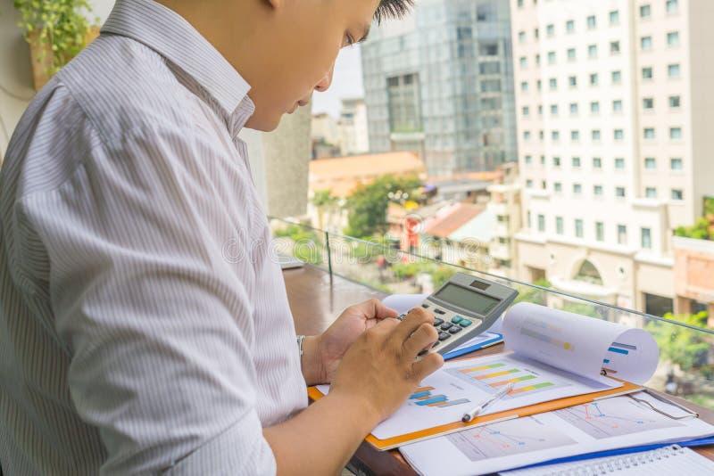 Ung affärsman som använder räknemaskinen för att kontrollera den finansiella rapporten fotografering för bildbyråer