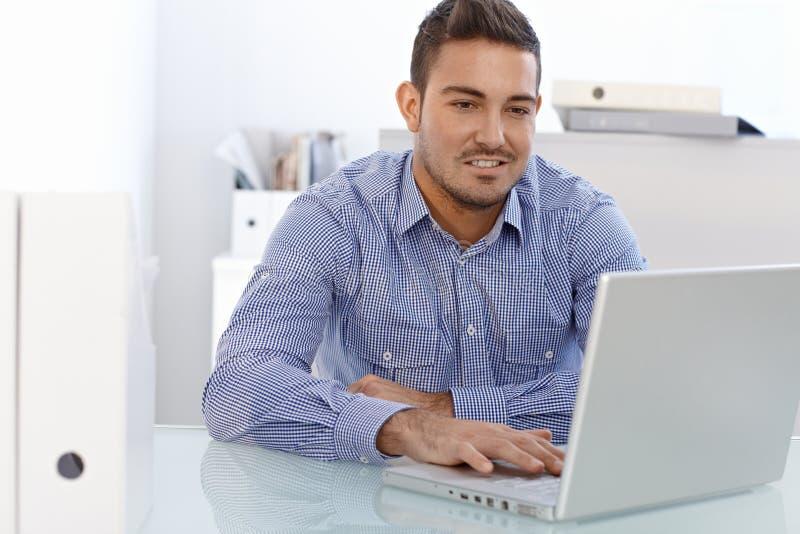 Ung affärsman som arbetar på bärbara datorn royaltyfri fotografi