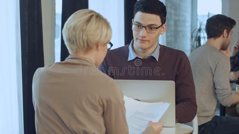 Ung affärsman som arbetar på bärbara datorn och affärskvinnan som arbetar med dokument som sitter på skrivbordet mitt emot honom arkivfoto