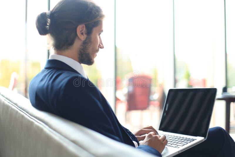 Ung affärsman som arbetar på bärbara datorn som sitter i hotelllobbyen som väntar på någon arkivfoton