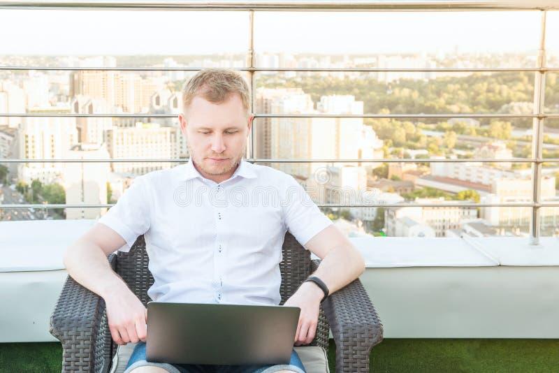 Ung affärsman som arbetar på datorbärbara datorn som sitter bekvämt på stol på kontorsterrassbalkongen med stads- landskap på lod arkivbild