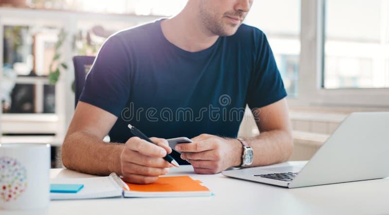 Ung affärsman som arbetar på hans skrivbord royaltyfria foton
