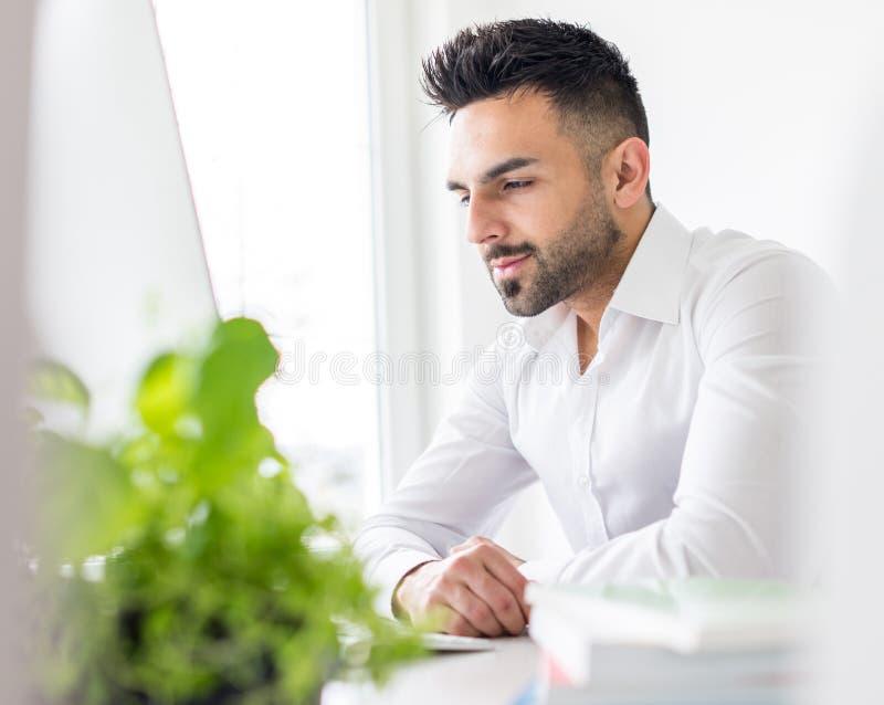 Ung affärsman som arbetar på kontoret på datoren arkivbilder