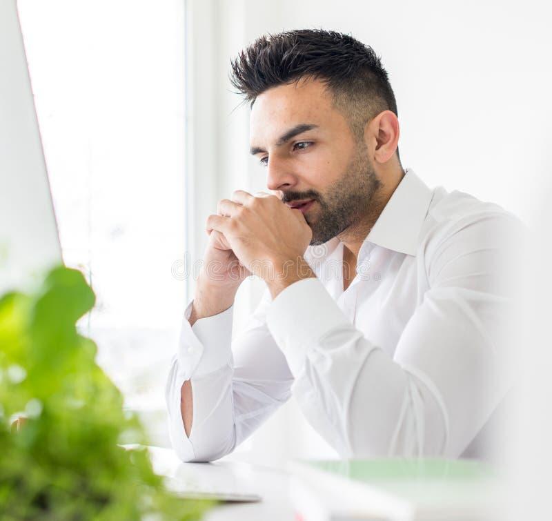 Ung affärsman som arbetar på kontoret på datoren royaltyfri bild