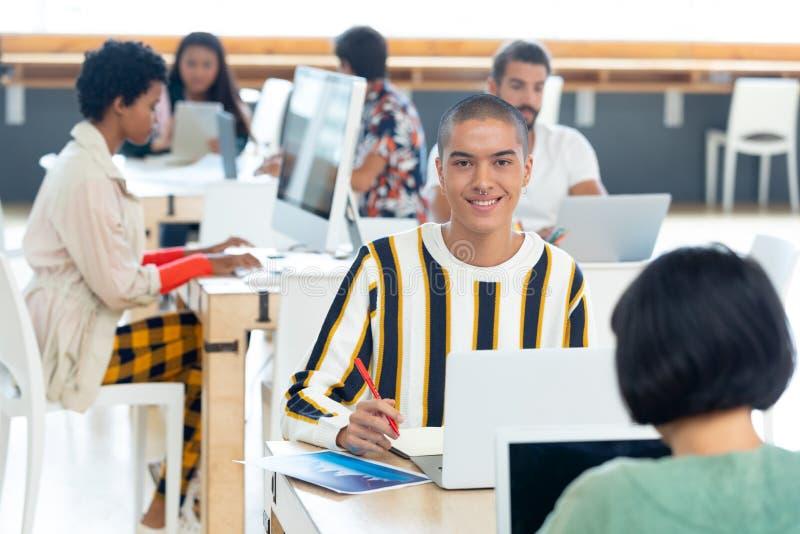 Ung affärsman som arbetar på skrivbordet i det moderna kontoret arkivfoton