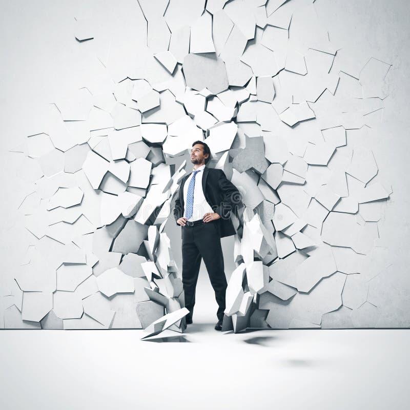 Ung affärsman som bryter ho en vägg arkivbild