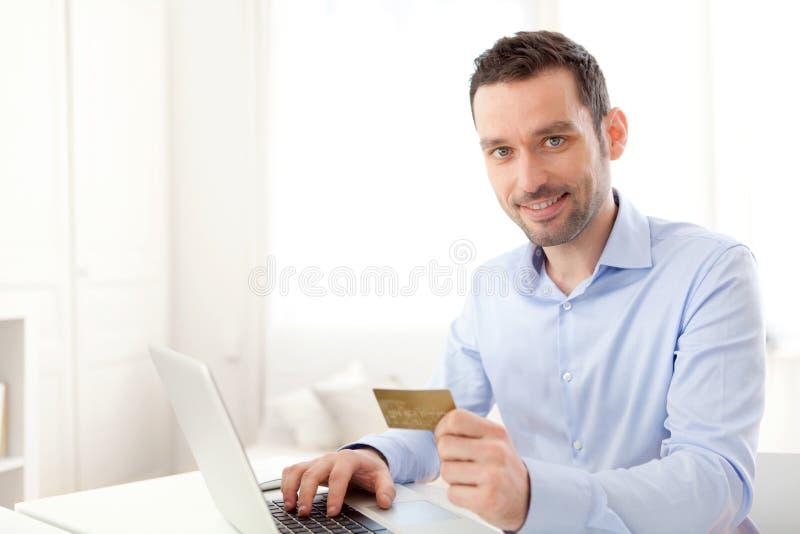 Ung affärsman som direktanslutet betalar med kreditkorten royaltyfri foto