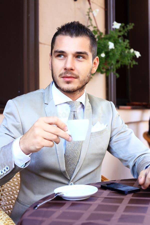 Ung affärsman som dricker en kopp kaffe, medan sitta arkivfoton