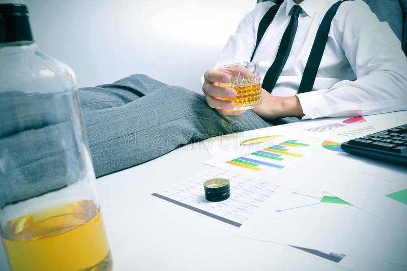 Ung affärsman som dricker i kontoret royaltyfri bild