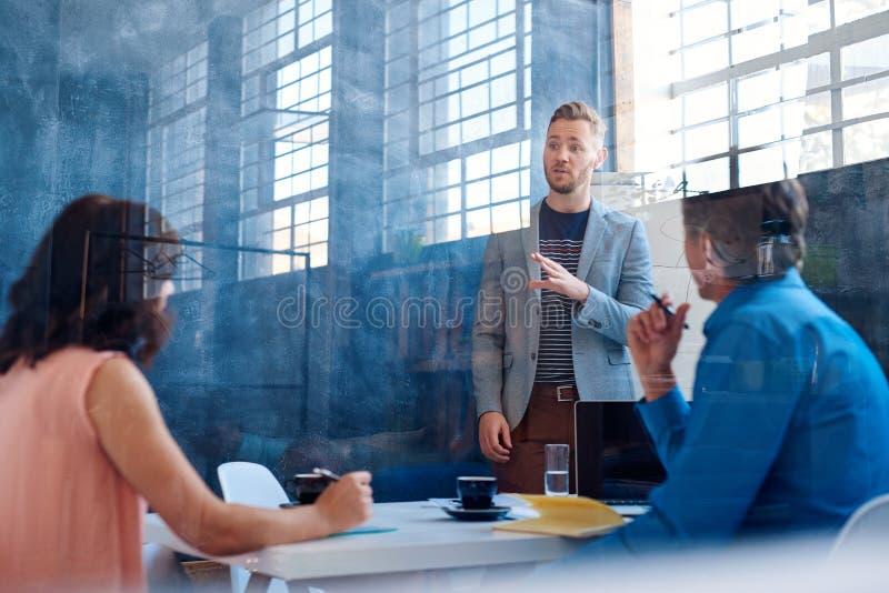 Ung affärsman som förklarar idéer till coworkers inom av ett kontor royaltyfria foton