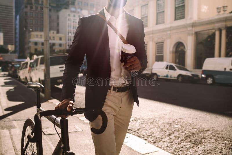 Ung affärsman som går att arbeta med cykeln arkivbild