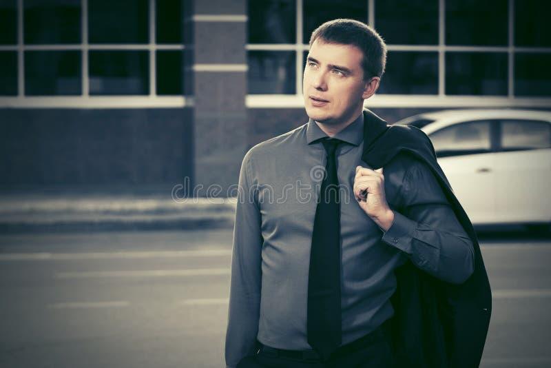 Ung affärsman som går i stadsgata arkivbild