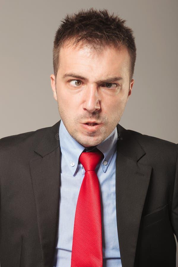 Ung affärsman som gör en ilsken framsida arkivbild