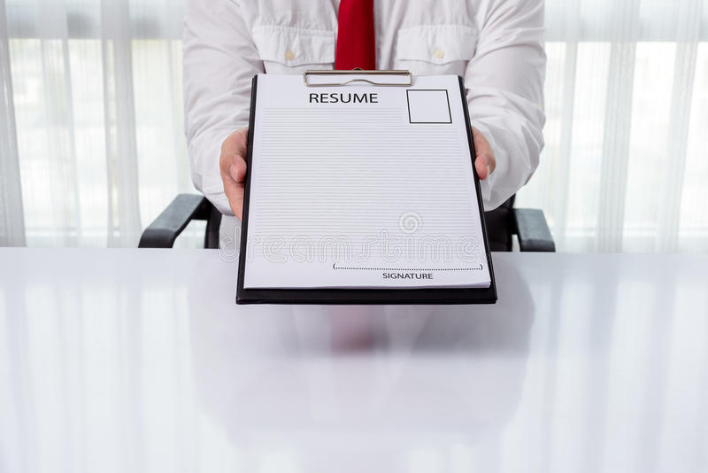 Ung affärsman som ger en meritförteckning royaltyfri bild