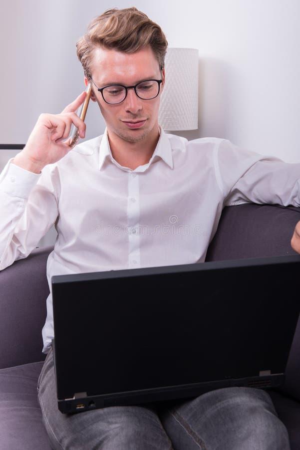 Ung affärsman som har en påringning, medan arbeta med bärbara datorn arkivfoton