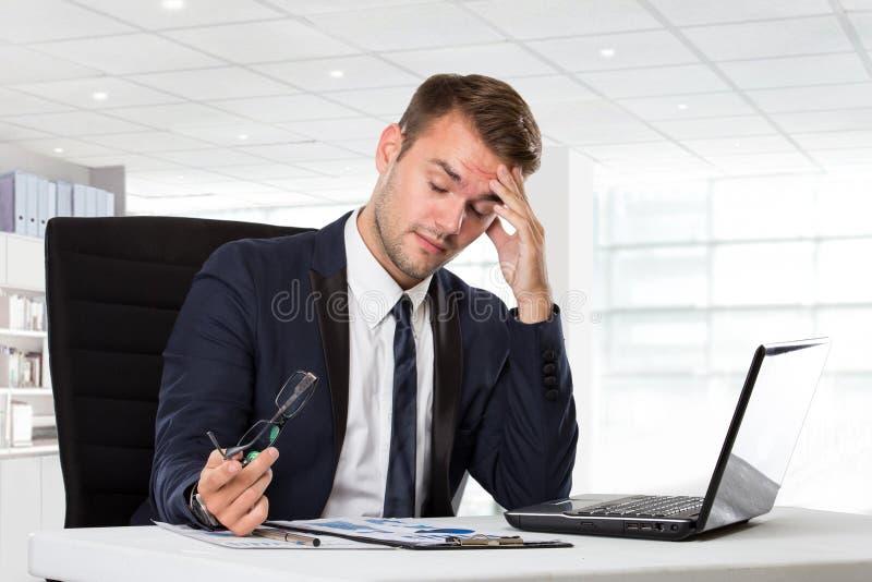 Ung affärsman som har huvudvärken som är stressad med hans arbete fotografering för bildbyråer