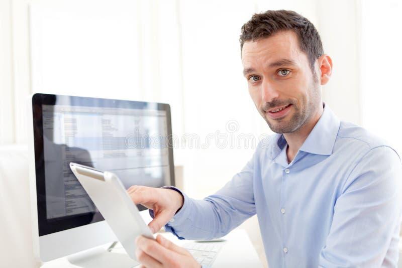 Ung affärsman som hemma arbetar på hans minnestavla royaltyfri fotografi