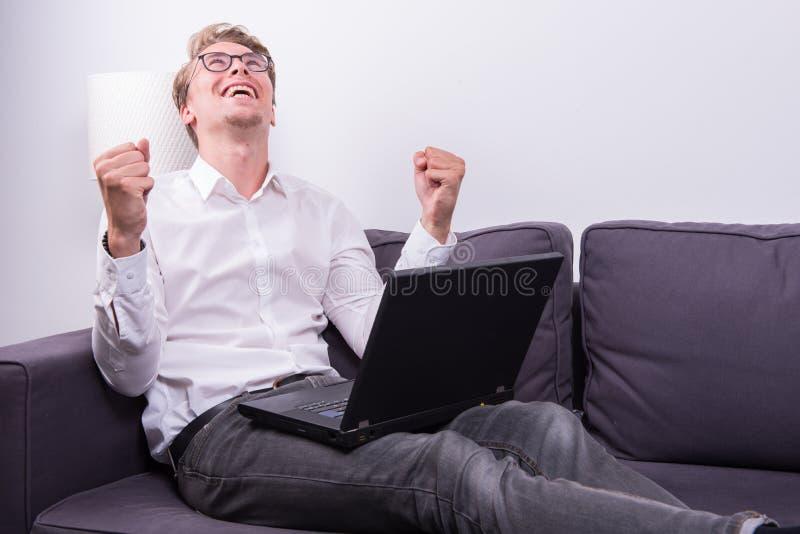 Ung affärsman som hurrar hans framgång, medan arbeta på bärbara datorn royaltyfri bild