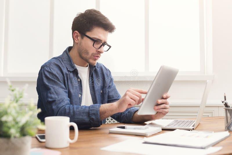 Ung affärsman som i regeringsställning arbetar med den digitala minnestavlan arkivfoto