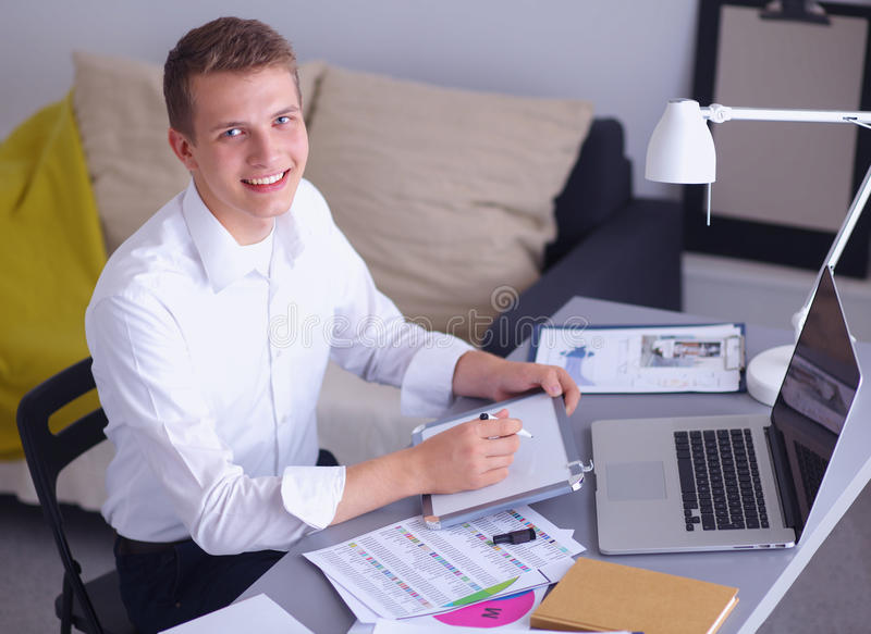 Ung affärsman som i regeringsställning arbetar och att stå nära arkivbild