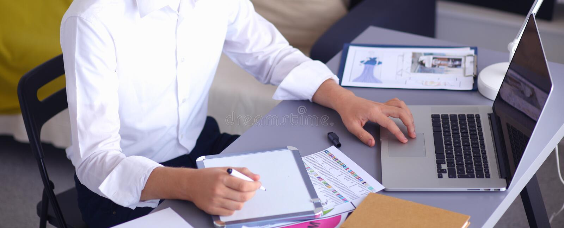 Ung affärsman som i regeringsställning arbetar, stående near skrivbord arkivfoto