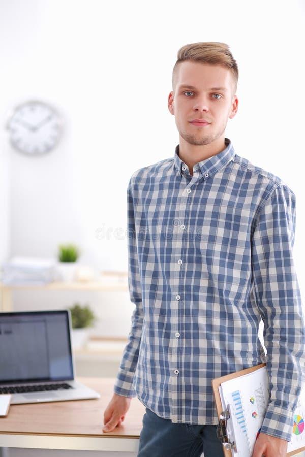 Ung affärsman som i regeringsställning fungerar och att sitta på skrivbordet royaltyfri bild