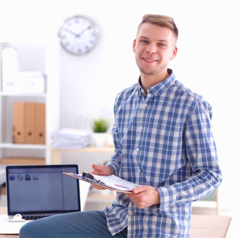 Ung affärsman som i regeringsställning fungerar och att sitta på skrivbordet royaltyfri foto