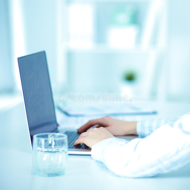 Ung affärsman som i regeringsställning fungerar och att sitta på skrivbordet royaltyfri fotografi