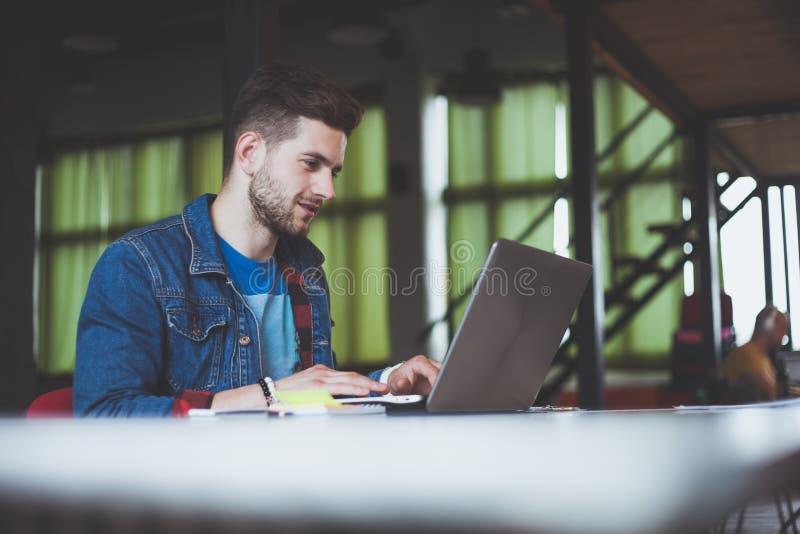 Ung affärsman som i regeringsställning fungerar och att sitta på skrivbordet och att se bärbar datordatorskärmen som ler arkivfoton