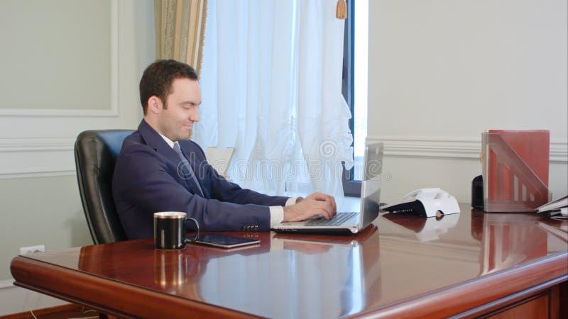 Ung affärsman som i regeringsställning ser datorbildskärmen under arbetsdags arkivfoton