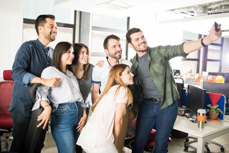 Ung affärsman som i regeringsställning tar selfie med laget arkivfoto