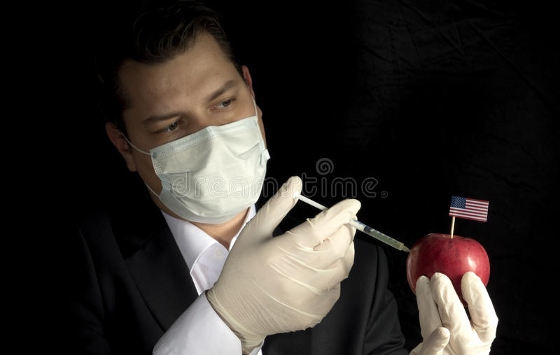 Ung affärsman som injicerar kemikalieer in i ett äpple med enigt arkivbilder