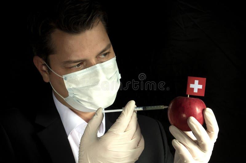 Ung affärsman som injicerar kemikalieer in i ett äpple med schweizare f royaltyfri fotografi