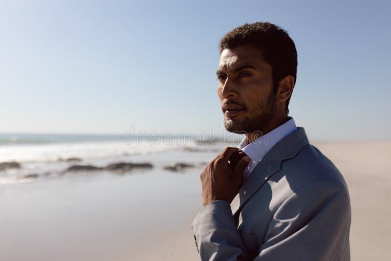 Ung affärsman som justerar hans band på stranden royaltyfri fotografi