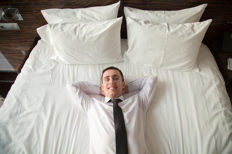 Ung affärsman som kopplar av i säng arkivfoto