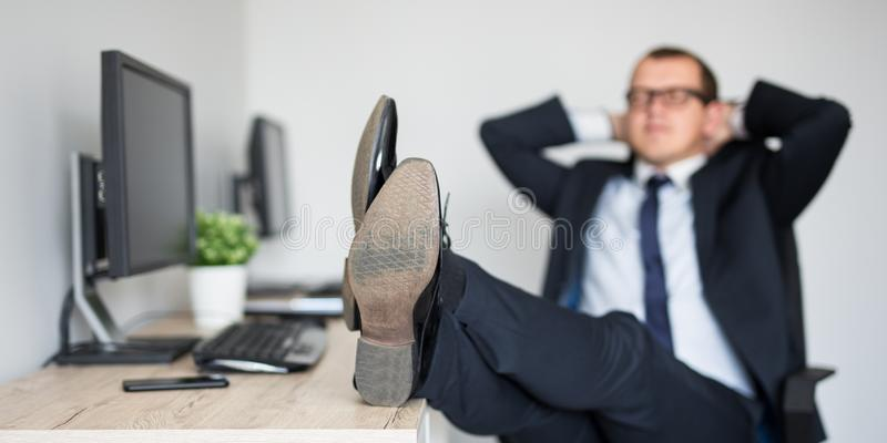 Ung aff?rsman som kopplar av med ben p? tabellen i modernt kontor royaltyfri foto