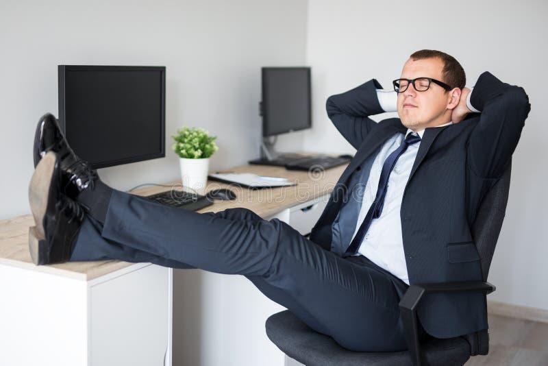 Ung affärsman som kopplar av på arbetsplatsen som i regeringsställning rymmer hans fot på skrivbordet arkivfoton