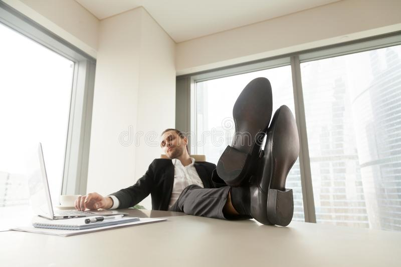 Ung affärsman som kopplar av på arbetsskrivbordet i modernt kontor fotografering för bildbyråer