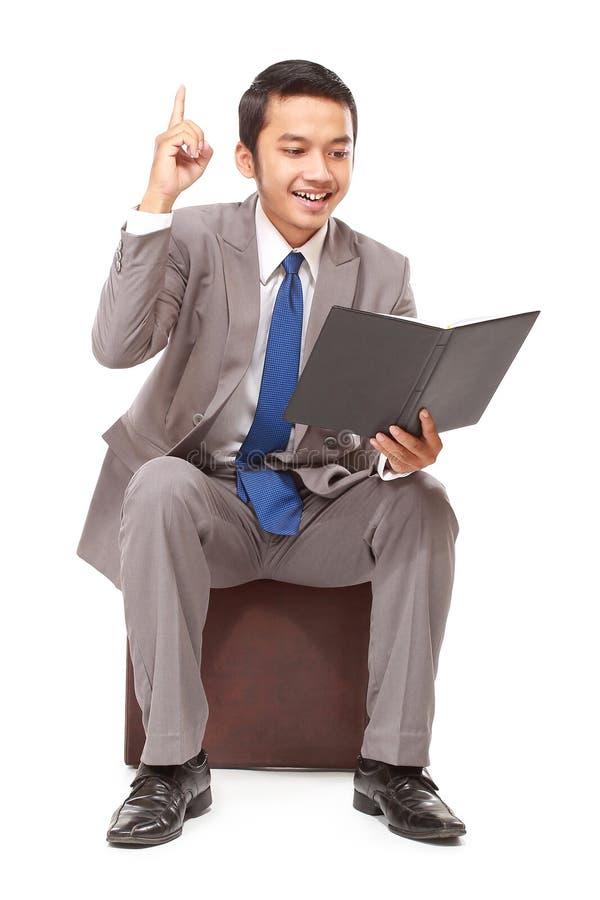 Ung affärsman som läser en bok och får idén arkivbild