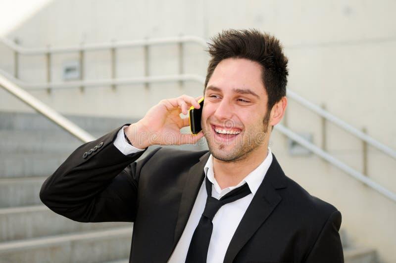 Ung affärsman som ler och talar på telefonen arkivfoto