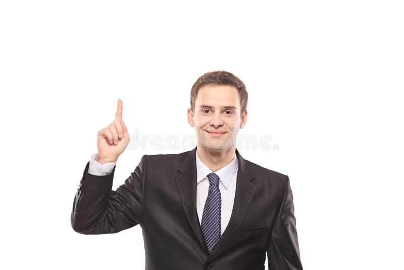 Ung affärsman som pekar upp med hans finger fotografering för bildbyråer