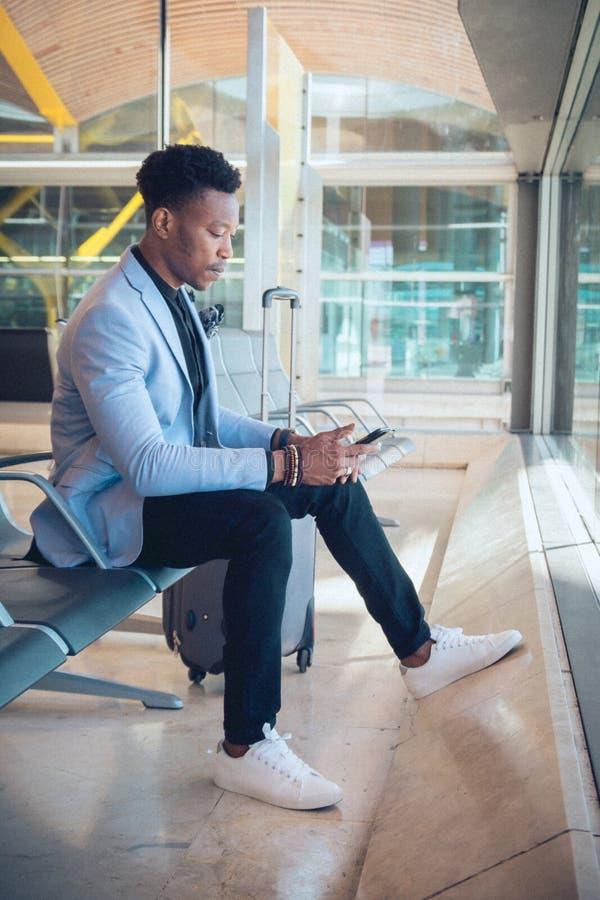 Ung affärsman som placeras i flygplatsen som kontrollerar en minnestavla och en ca royaltyfri foto