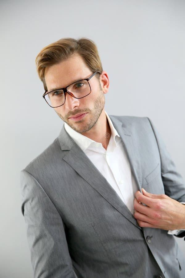 Ung affärsman som plattforer på grå bakgrund arkivfoto