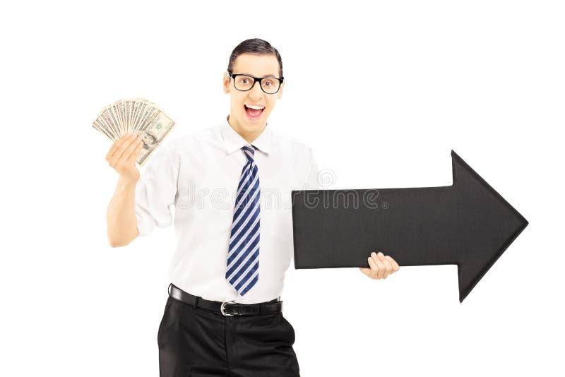 Ung affärsman som rymmer en pil som pekar till rätten och dolen royaltyfri bild