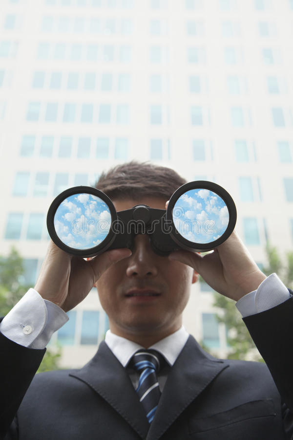 Ung affärsman som ser in i avståndet till och med kikare med moln och himmel i linserna av kikaren royaltyfri foto