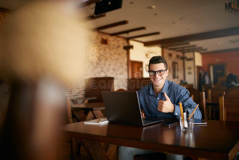 Ung affärsman som ser kameran med bärbara datorn i kafé Le mannen i stilfulla exponeringsglas och ila tillfälligt göra för skjort royaltyfria bilder