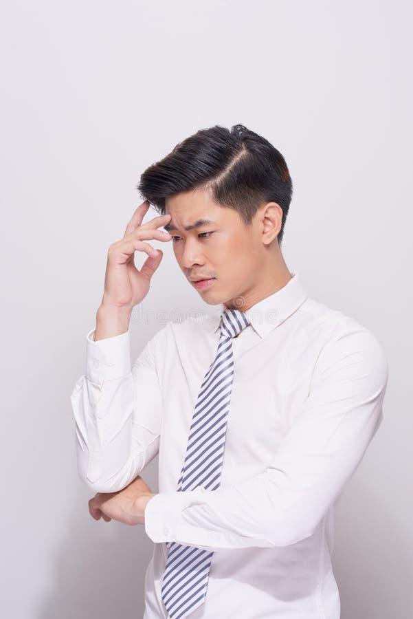 Ung affärsman som ser ner isolerad på vit bakgrund royaltyfri fotografi
