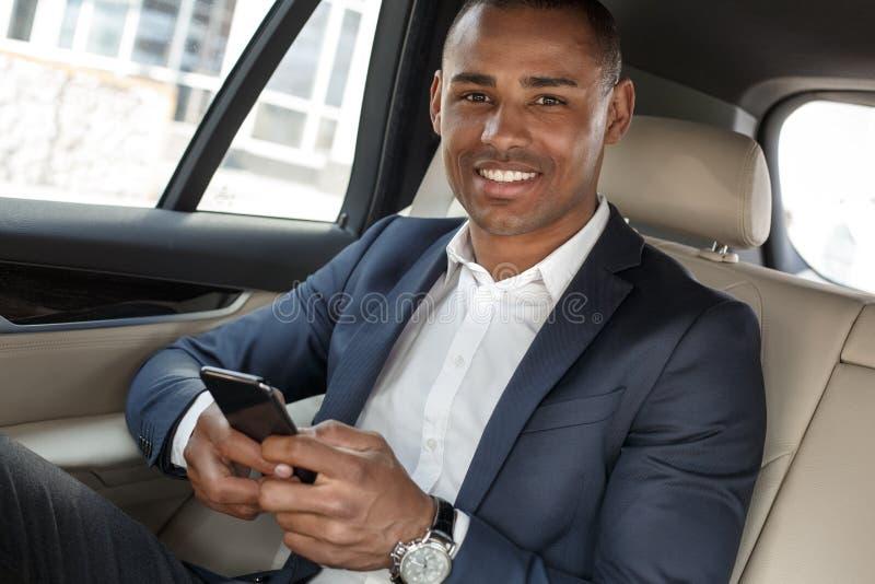 Ung affärsman som sitter på baksätet i bil genom att använda smartphonen som ser lycklig närbild för kamera royaltyfri fotografi