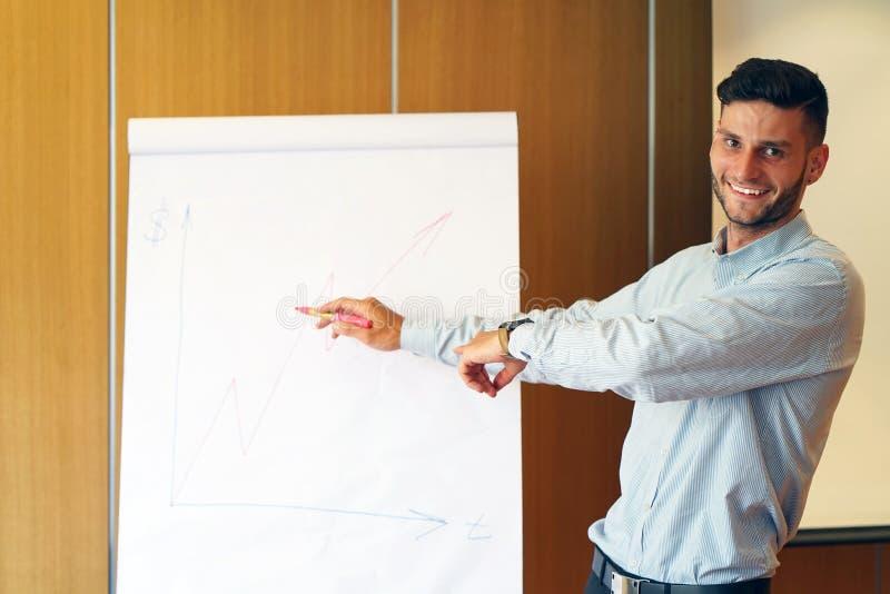 Ung affärsman som står det near flipdiagrammet arkivbild